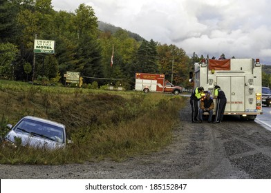 DWIGHT, ONTARIO - OCTOBER 4, 2009: Firetruck and paramedics with an ambulance vehicle assisting the driver at the scene of an accident