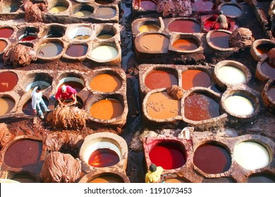 Dye reservoirs and vats in traditional tannery of city of Fez, Morocco, with men working in the dye vats (viewed from from a Terrace)