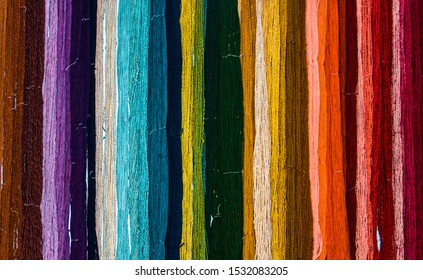 dyed colored yarn hanging on wall in bunches forming a rainbow pattern