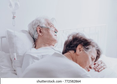 Dying elderly man with drip and nasal cannula at hospital and his hopeful wife