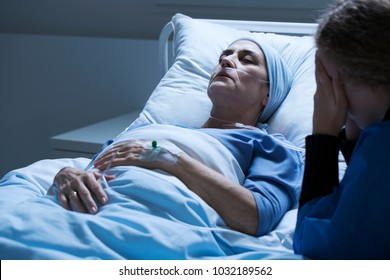 Dying elderly woman with tumor and crying daughter in a clinic