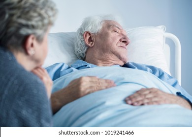 Dying man lying in hospital bed. Palliative care for an elderly patient