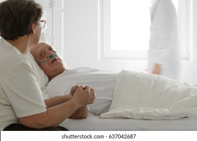 Dying man with nasal cannula and his worried supporting wife