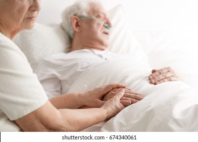 Dying senior man laying on a bed and his wife holding his hand