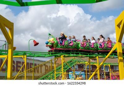 Dymchurch England - August 19 2019; Amusement Park  catapillar roller coaster being ridden by adults and children.
