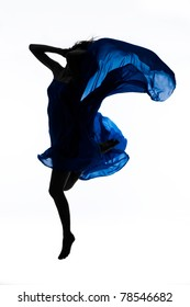 Dynamic, beautiful woman wrapped in blue fabric jumping over white background; a lot of copyspace available.