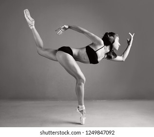 Dynamic black and white view of ballet dancer lifting leg up with harmony, conceptual power balance, flexibility lightness, stage indoors. Artistic female stretching, body shape, energy fitness.