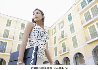 Dynamic businesswoman walking through a European city's square, turning back.