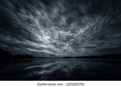 Dynamic clouds in the night over the lake lit by full moon, long exposure shot