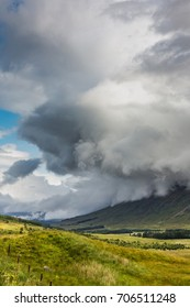 Dynamic and dramatic storm clouds over Scottish Highlands and lakes. Vertical full frame landscape with low horizon