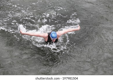 dynamic and fit swimmer in cap and wetsuit breathing performing the butterfly stroke in dark ocean water