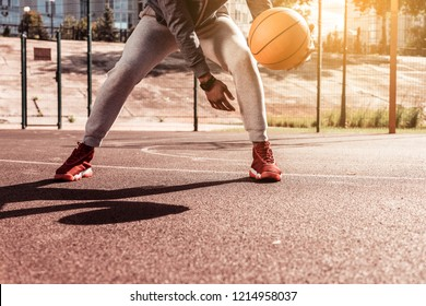 Dynamic game. Nice young man holding a basketball ball while playing a game