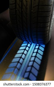 Dynamic and high tech concept of automobile tire with lit blue treads on ground