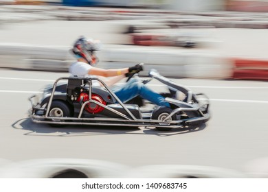 Dynamic image of teenage boy, moving fast by a go-kart, with motion blur effect.