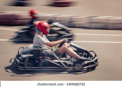 Dynamic image of two competitive, moving fast, go-karts, with motion blur effect.