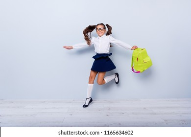 Dynamic images, back to school concept. Full length, legs, body, size portrait of adorable brunette girl with yellow rucksack joyfully jumping isolated on light gray background