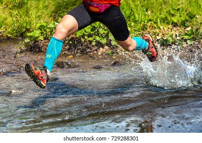 Dynamic man trail running in the mountain, jumping over a creek
