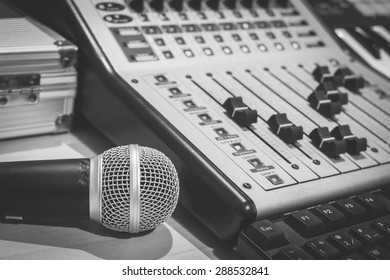 dynamic microphone, digital studio mixer & keyboard synthesizer, focus on mic. B&W filter for music recording, radio / tv broadcasting  background