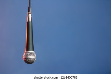 dynamic microphone with a spherical protective mesh is hanging on the wire from above, backlit with red light on a blue monophonic background