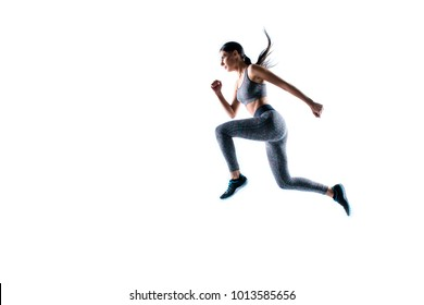 Dynamic movement. Full size side profile view portrait of strong sporty muscular beautiful running focused woman wearing tight sport clothing, isolated on white background, natural light, copy-space