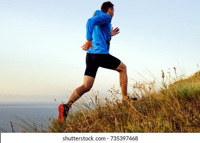 dynamic running uphill male athlete runner in background of sea and sky