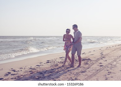 Dynamic shot of happy smiling couple. Focus on guy. Walking on the beach. Holding each other and laughing