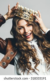 dynamic smiling woman in golden crown with pearls in leather jacket