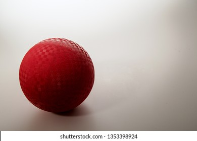 Dynamic studio shot of single red playground ball (as used in dodge ball, handball, kickball, gym or playground activities, made of rubber) on gradated white background, with room for type of copy.