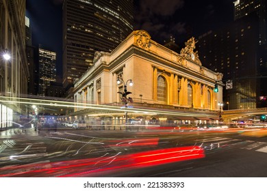 Dynamic wide angle view on the illuminated Grand Central Terminal at night with red light trails on the streets in New York, USA, America