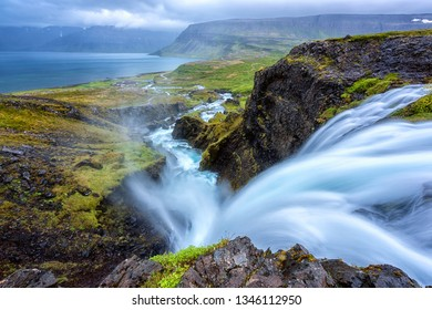 Dynjandi waterfall, Iceland, amazing landscape. Stunning view of falling water in the canyon from the top to the Dynjandisvogur bay and Arnarfjordur fjord, Westfjords of Iceland, travel background