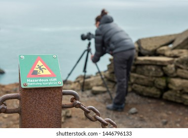DYRHOLAEY, ICELAND - MAY 21, 2019: Photographer ignoring a hazardous cliff sign and passing over the fence in the prohibited dangerous area near the rocks of Dyrholaey