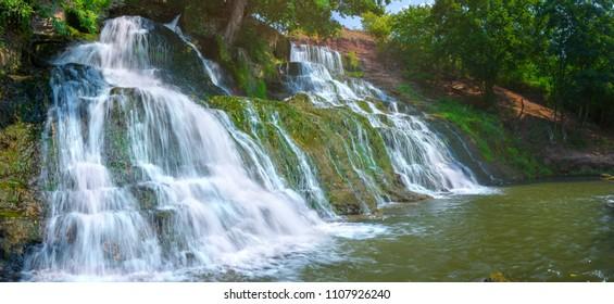 Dzhurynskyi or Chervonogorod cascading waterfalls. Outskirts Nyrkiv village on the Dzhuryn river. Zalischiki. Ternopil region. Ukraine. A daylight scene longexposure with ND filters technics.