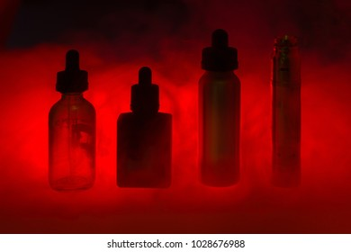 E cigarette with three e-liquid in the smoke on a dark red background. E-juice in colour from vape. Alternative to smoking