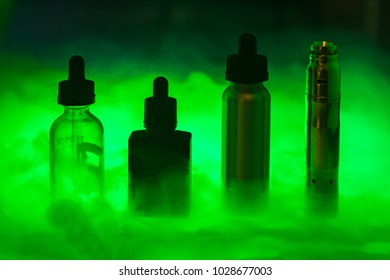 E cigarette with three e-liquid in the smoke on a dark green background. E-juice in colour from vape. Alternative to smoking