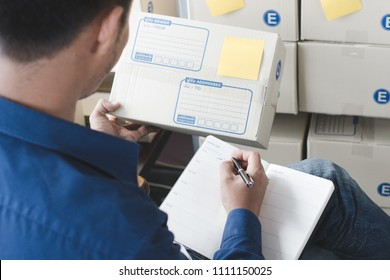 e commerce business concept. Back view of Business owner checking ordered from client in application in mobile phone and taking note to package notes preparation to send to post.