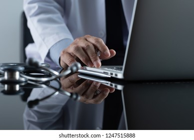 E health, medical online, medical technology concept. Doctor or medical student working on laptop computer with stethoscope on mirror desk in office, copy space, close up