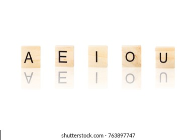 A E I O U, vowel word  with reflection, on wooden blocks on white background, Isolated.