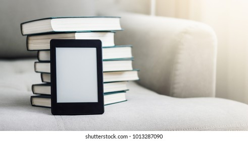 E reader over big stack of books.