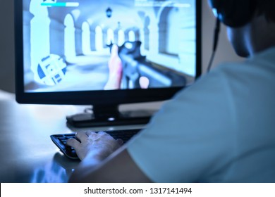 E sports and gaming concept. Gamer playing FPS video game with computer and wearing headphones. Professional videogame player or competitor in event. Man streaming online. Pro esports.