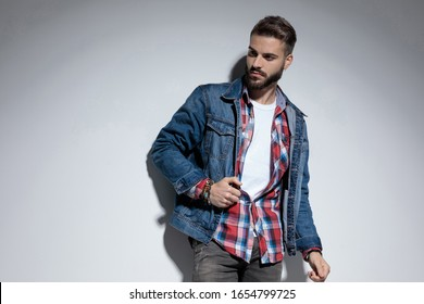 Eager fashion model curiously looking away and fixing his jacket while standing on gray studio background