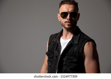 Eager man looking forward while wearing sunglasses and a black jeans vest, standing on gray studio background