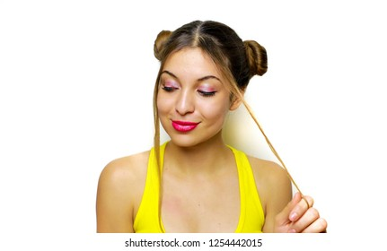 Eager mischievous young woman with hair chignons twirling a lock of hair and looks to the side like she has an idea