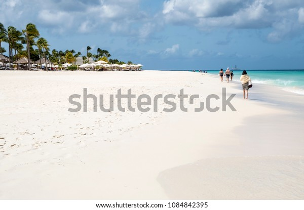 Eagle Beach, Aruba - April 10, 2018: People Walking Along Beautiful Eagle Beach That Goes On Forever ... In the Distance There Is a Offshore Drilling Station