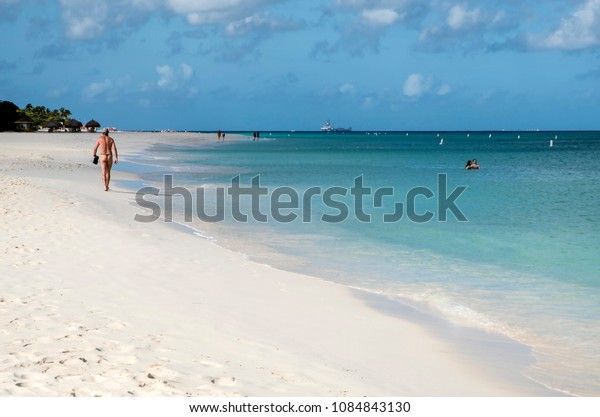 Eagle Beach, Aruba - April 10, 2018: People Walking Along Beautiful Eagle Beach That Goes On Forever ... In the Distance There Is a Offshore Drilling Station ... In the Foreground, There Is a View of