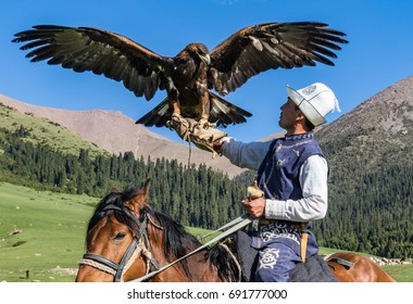 Eagle Hunter holds his eagles on horseback, ready to take flight in Kyrgyzstan on May 29, 2017