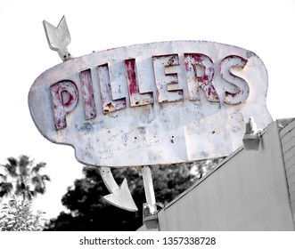Eagle Rock, CA USA April 17, 2017 This old wooden sign was found in Eagle Rock CA.  It is distressed and rather shabby.  It has raised red letters and an arrow running thru it. A bedding business?