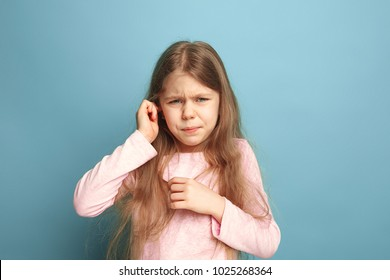 The Ear ache. The sad teen girl with headache or pain on a blue studio background. Facial expressions and people emotions concept. Trendy colors. Front view. Half-length portrait