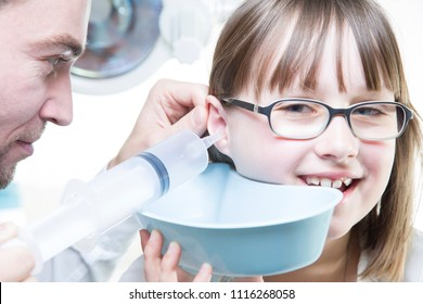 Ear irrigation and earwax removal. Young male laryngologist doctor performing ear wash on a child patient with syringe and emesis basin
