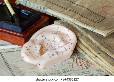 Ear model and needle for ear acupuncture with ancient medicine books at the background (Translation: all the characters are no text, but individual names of each acupuncture point.)