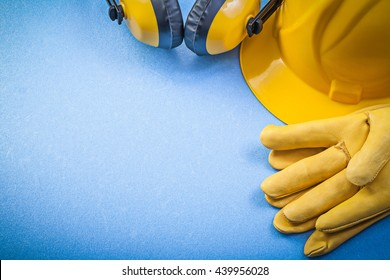 Ear muffs leather safety gloves building helmet on blue background construction concept.